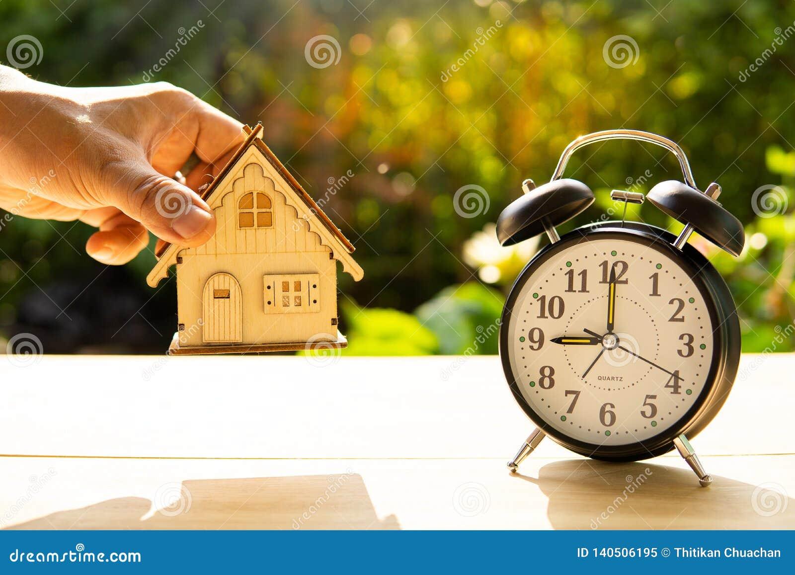Modelo da casa da captura do homem e a pilha do despertador no fundo de madeira da tabela e do por do sol no momento da mostra do