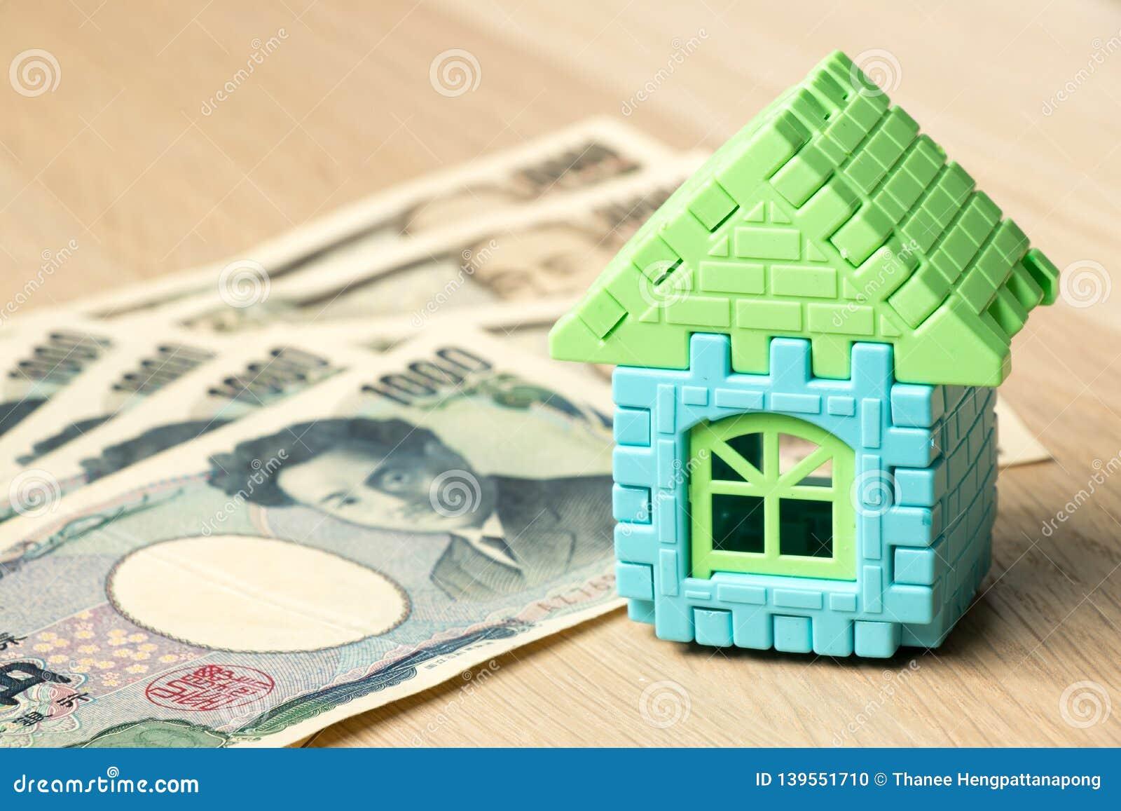 Modelo da casa com a cédula do iene japonês na tabela de madeira