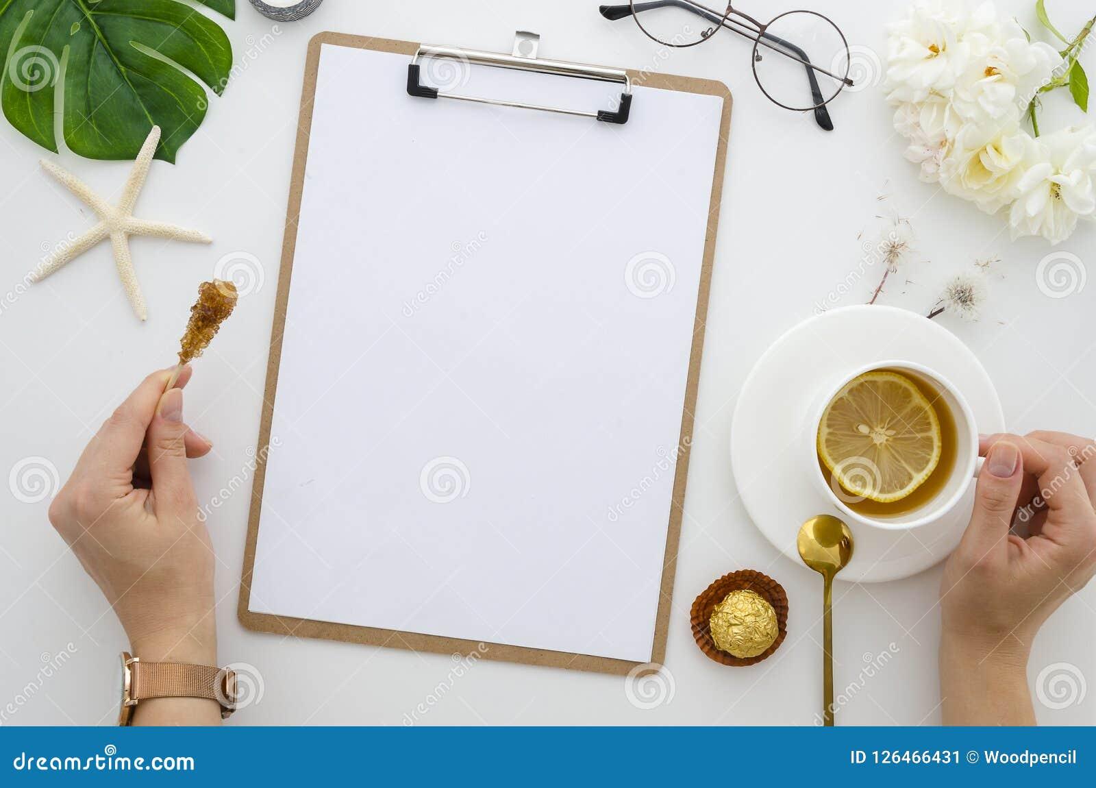 Modelo da placa de grampo da mesa de escritório da vista superior A menina está guardando o copo do chá com limão, espaço de trab