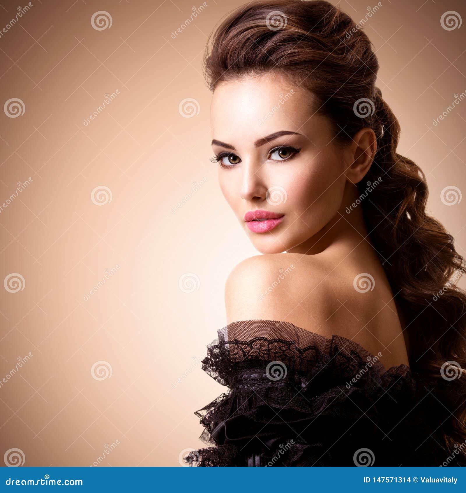 Modelo de forma no vestido dourado Modelo com um cabelo encaracolado longo Penteado criativo
