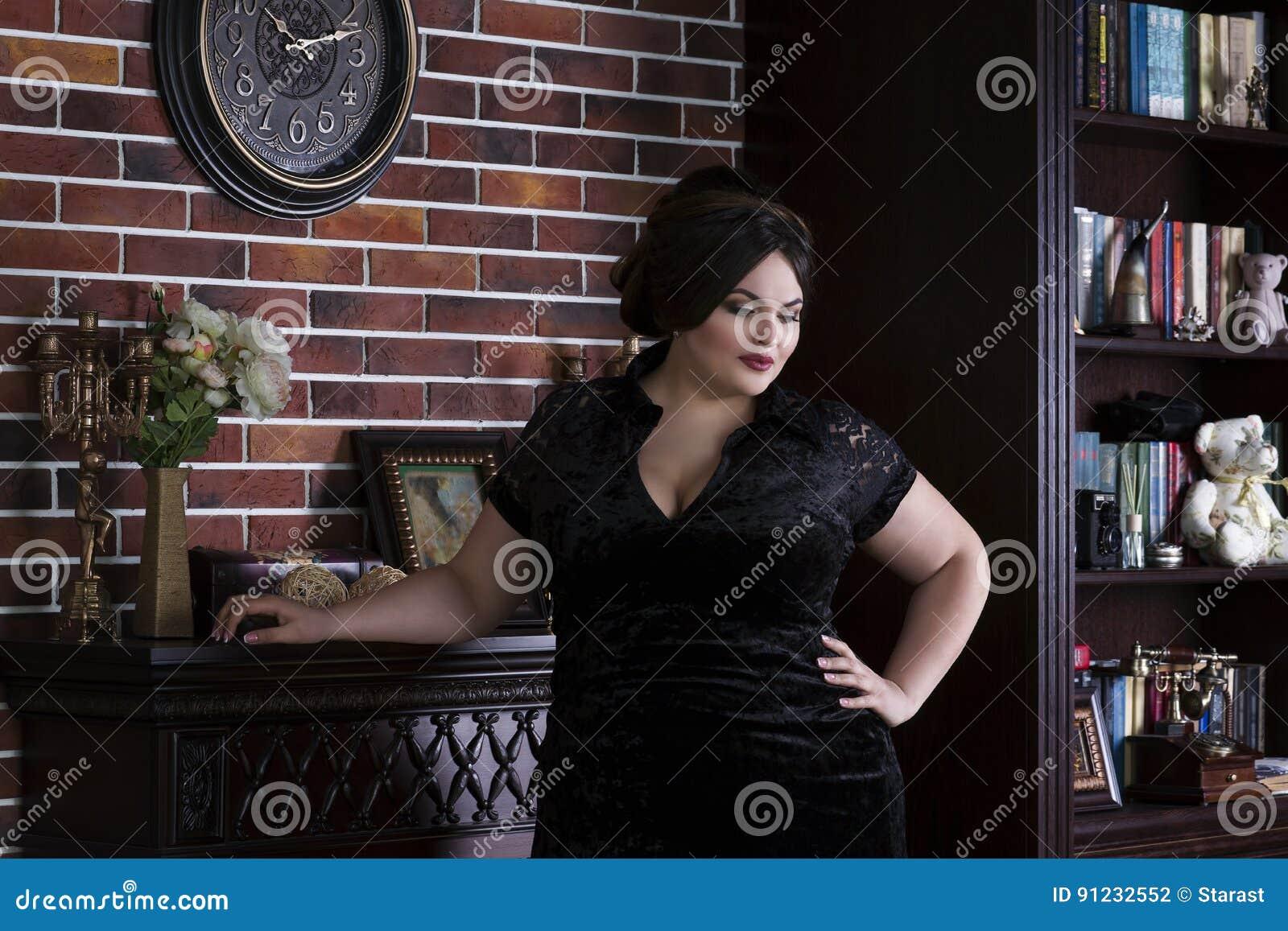 Modelo de forma positivo do tamanho no vestido de noite preto, mulher gorda no interior luxuoso, corpo fêmea excesso de peso