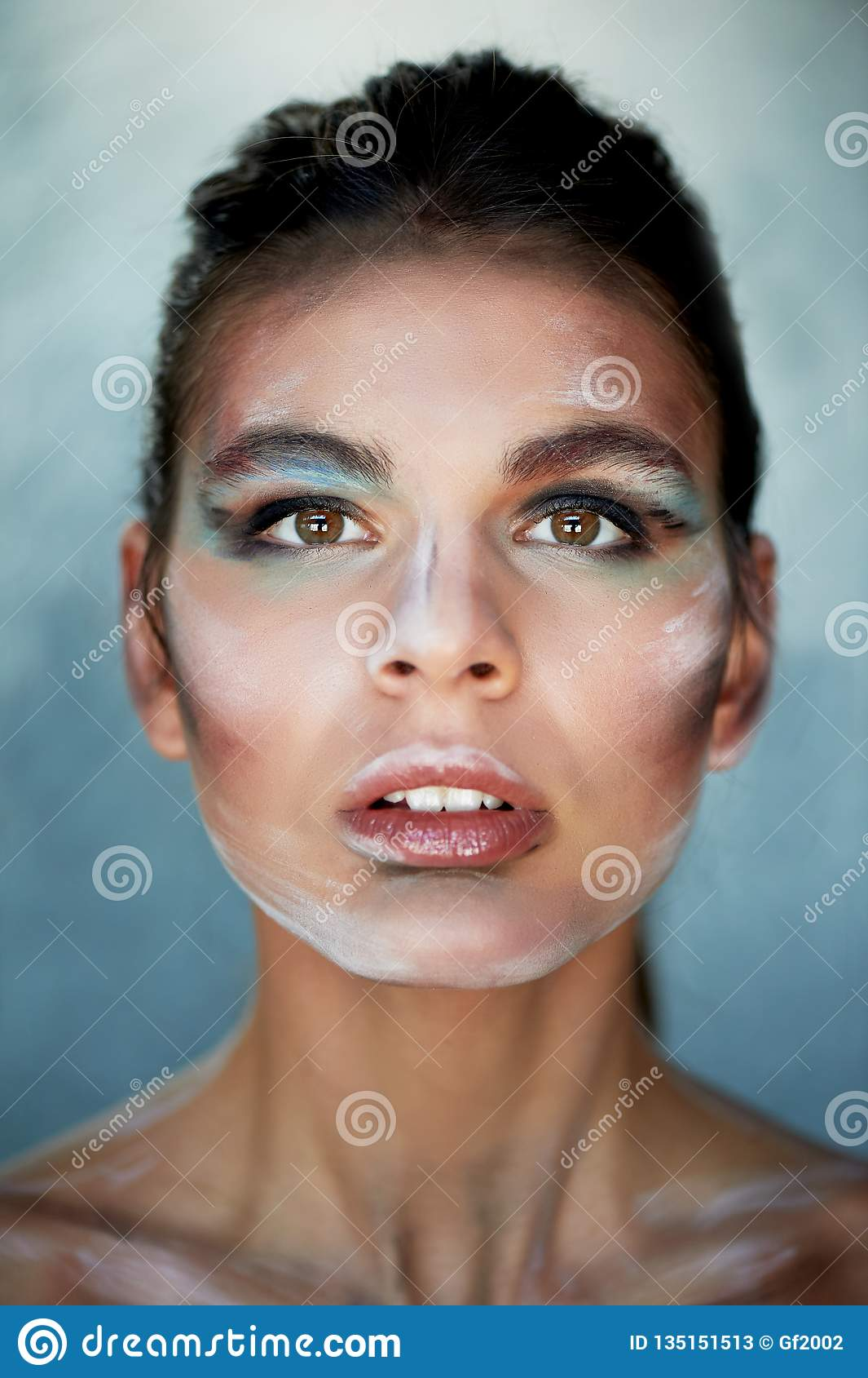 Modelo de la muchacha con el maquillaje creativo, movimientos de la pintura en la cara Persona creativa Labios entornados, cabeza