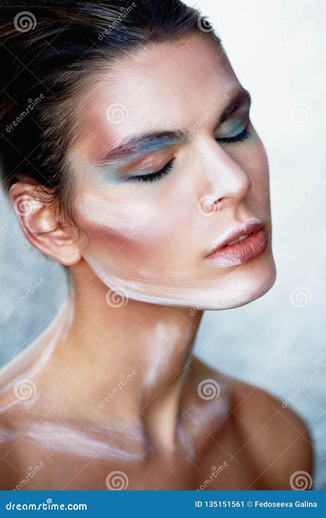 Modelo de la muchacha con el maquillaje creativo, movimientos de la pintura en la cara Persona creativa Los ojos se cerraron, est