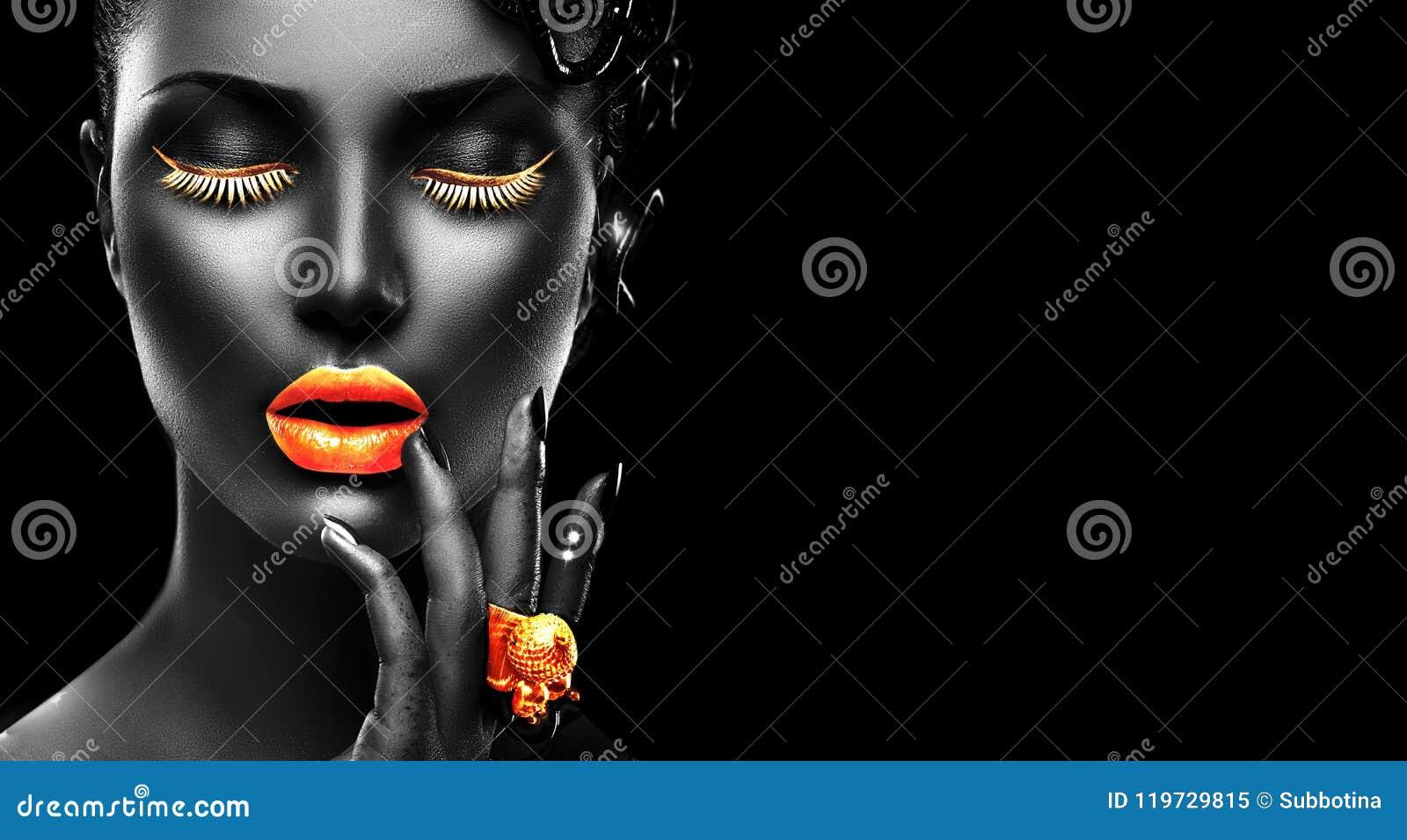 Modelo de moda con la piel negra, los labios de oro, las pestañas y la joyería - anillo de oro a mano En fondo negro