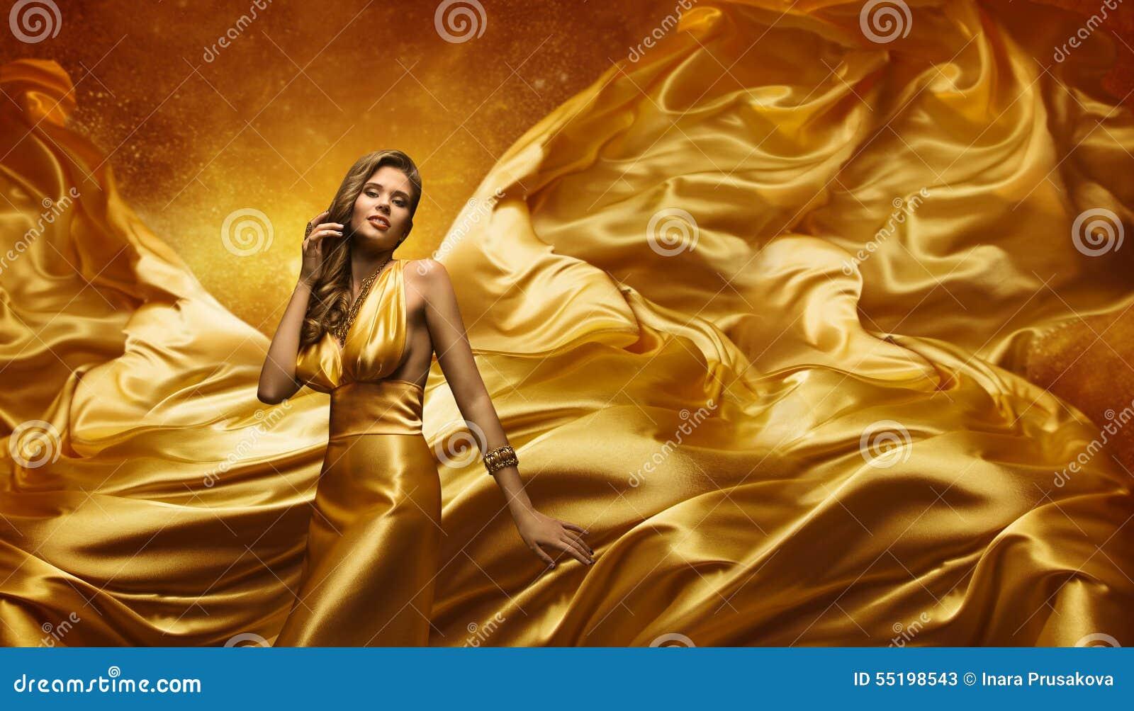Modelo de moda en el vestido del oro, mujer de la belleza que presenta el paño del vuelo