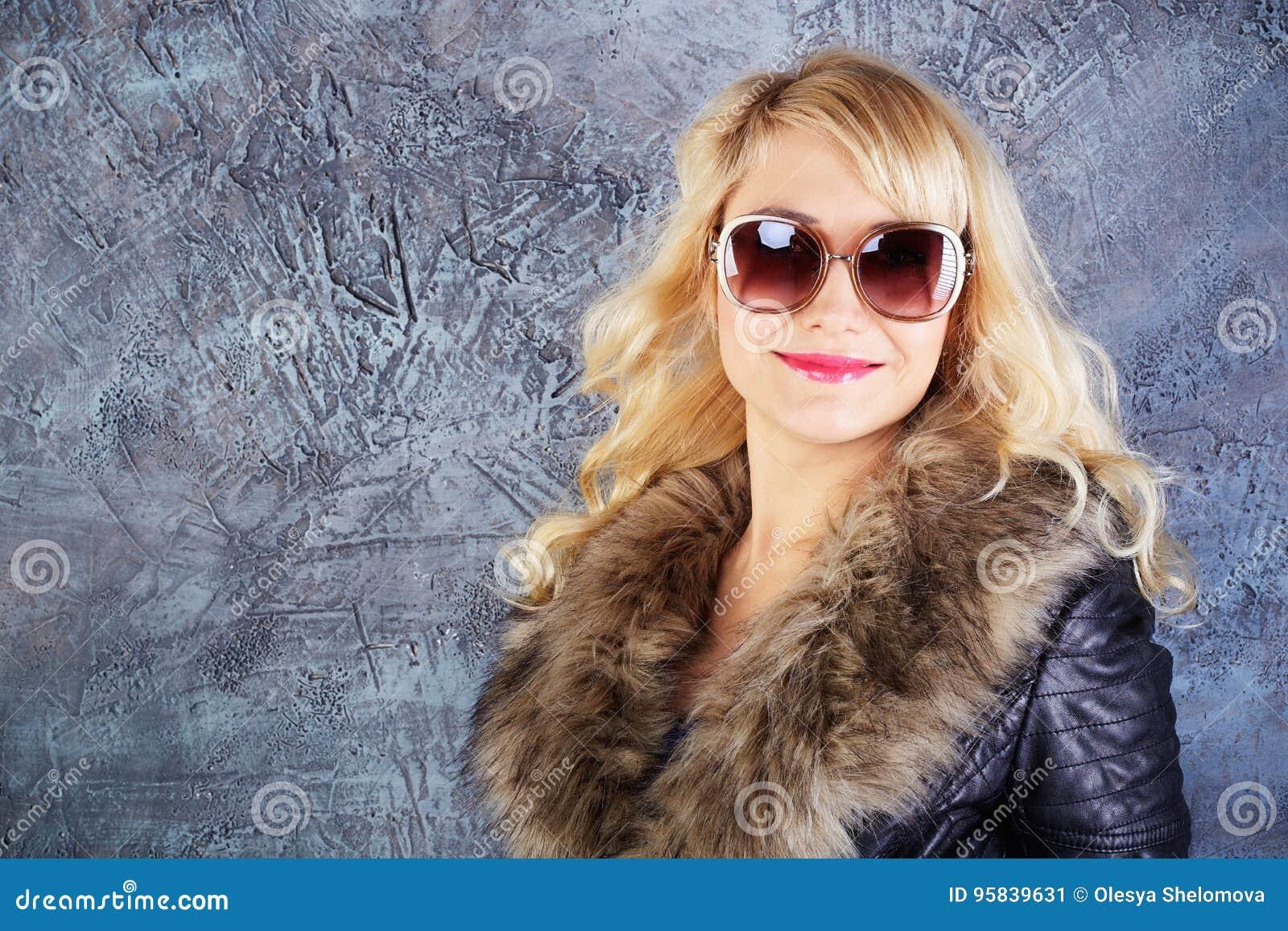 Modelo de moda feliz que presenta en capa y gafas de sol