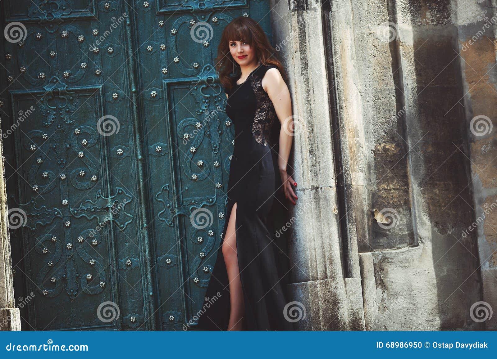 Modelo de moda integral en el vestido negro que presenta en el ne de la calle