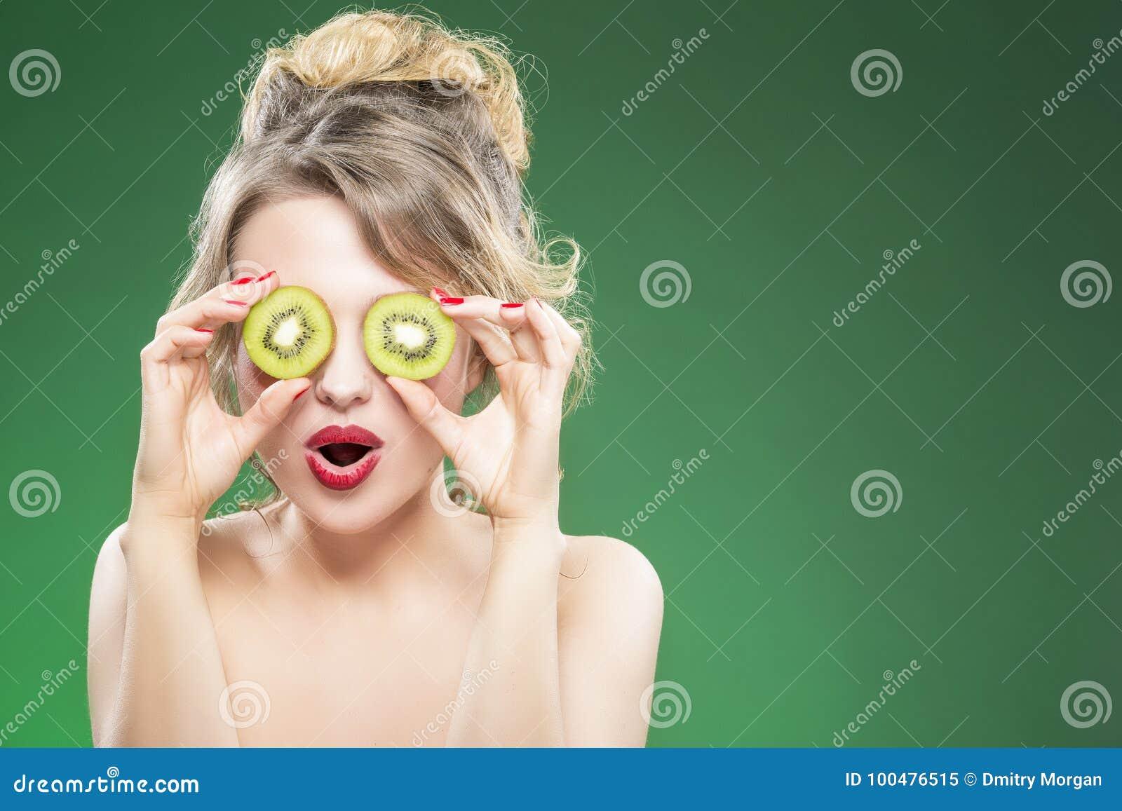 Modelo de Nude caucasiano Making Faces ao levantar com dois Kiwi Slices