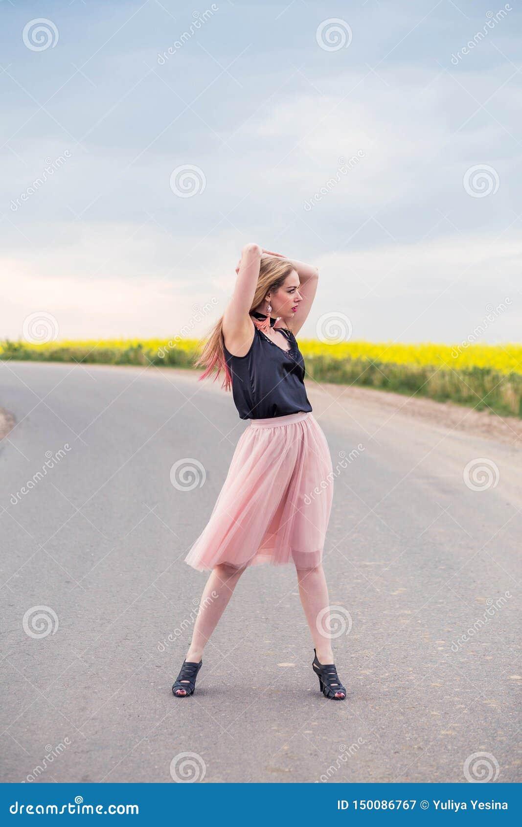 Modelo elegante da menina em uma saia do tule e em uma parte superior preta que levantam na estrada