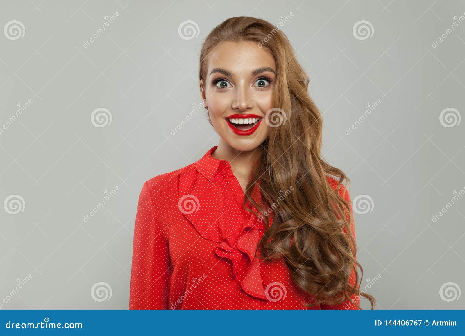Modelo emocionado que sonríe en el fondo blanco Retrato sorprendido j?venes de la mujer