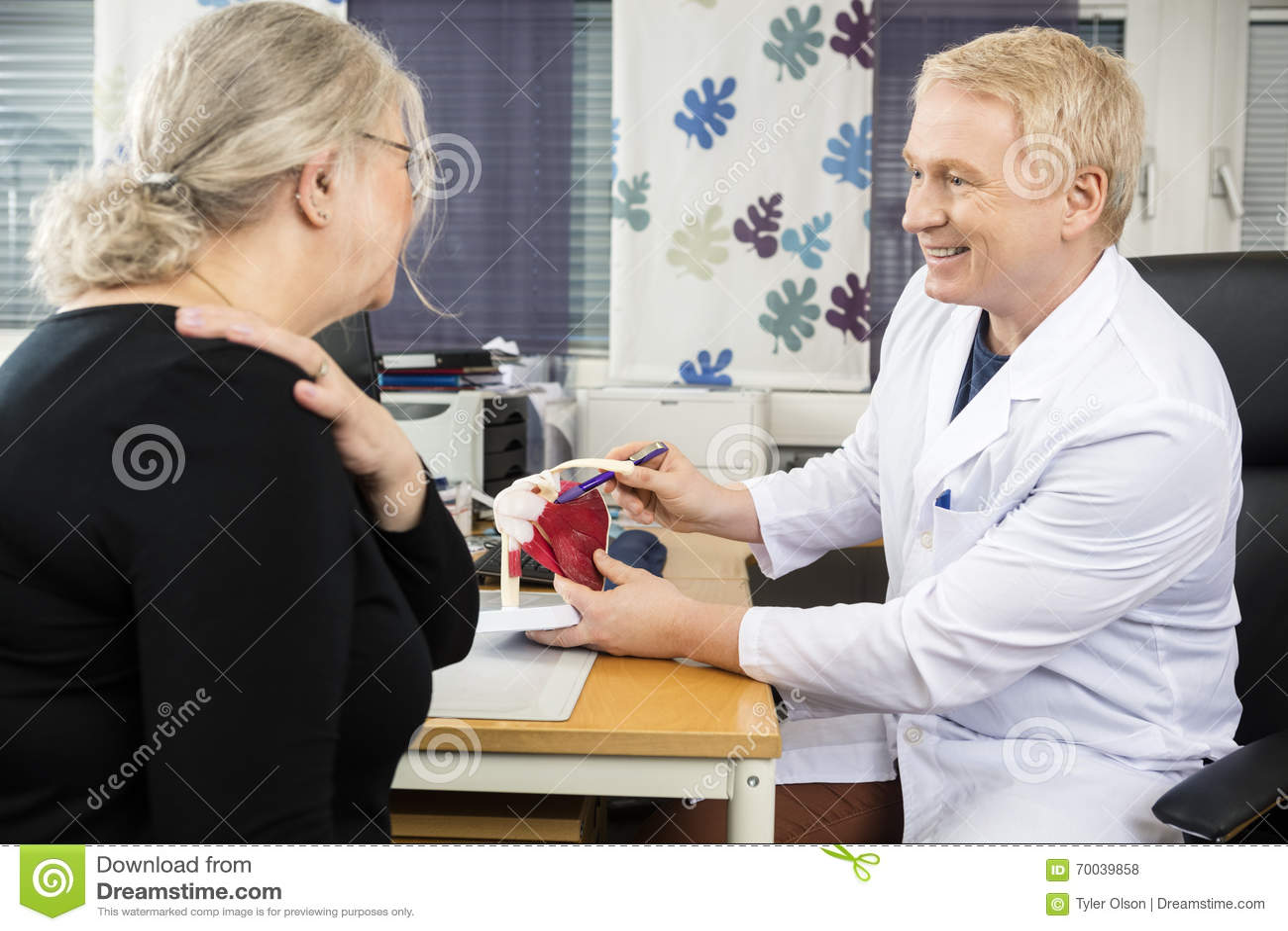 Modelo While Explaining del puño de rotor del doctor Pointing At Shoulder