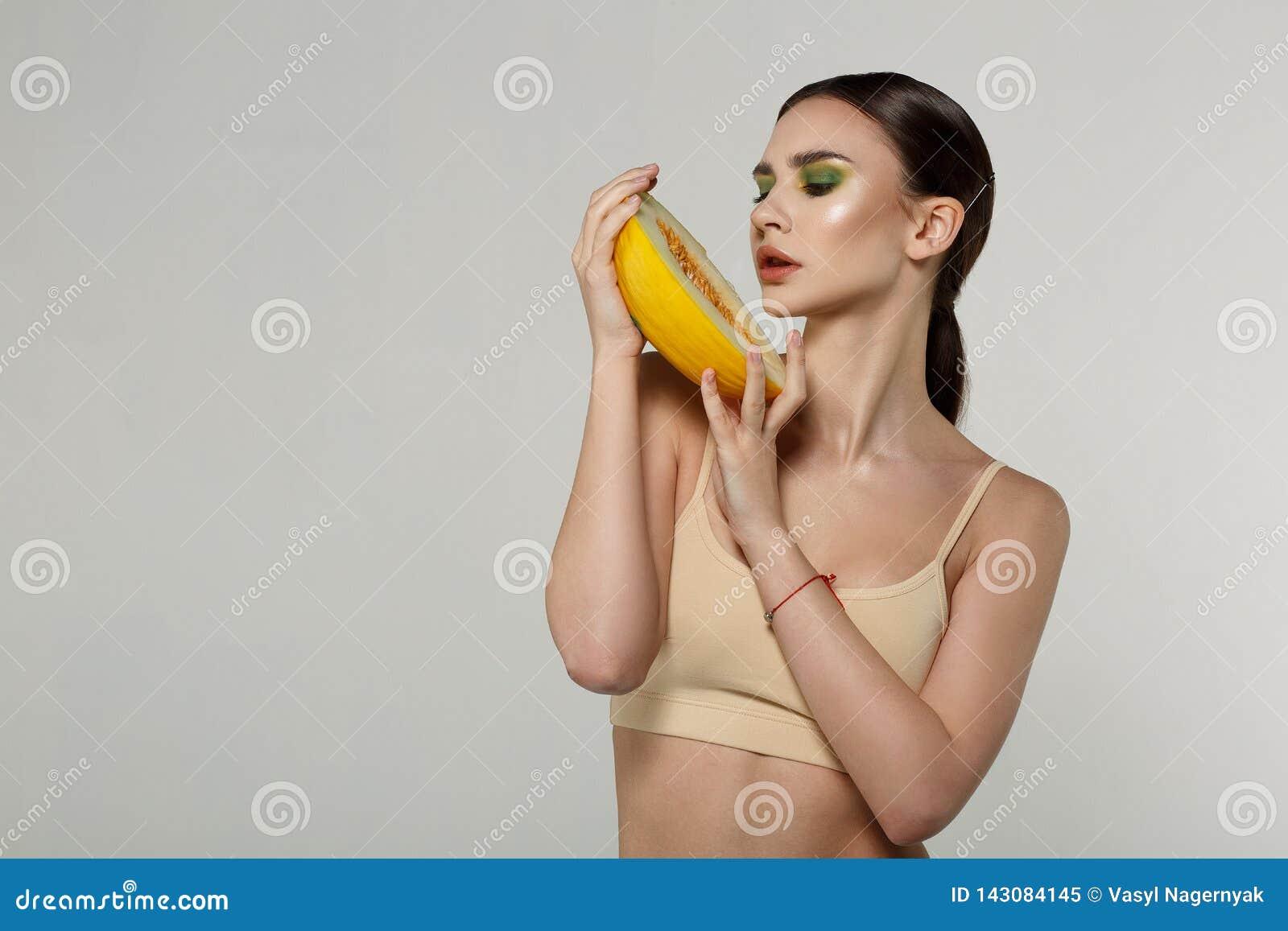 Modelo fêmea novo com a pele natural saudável que olha o melão cortado em suas mãos