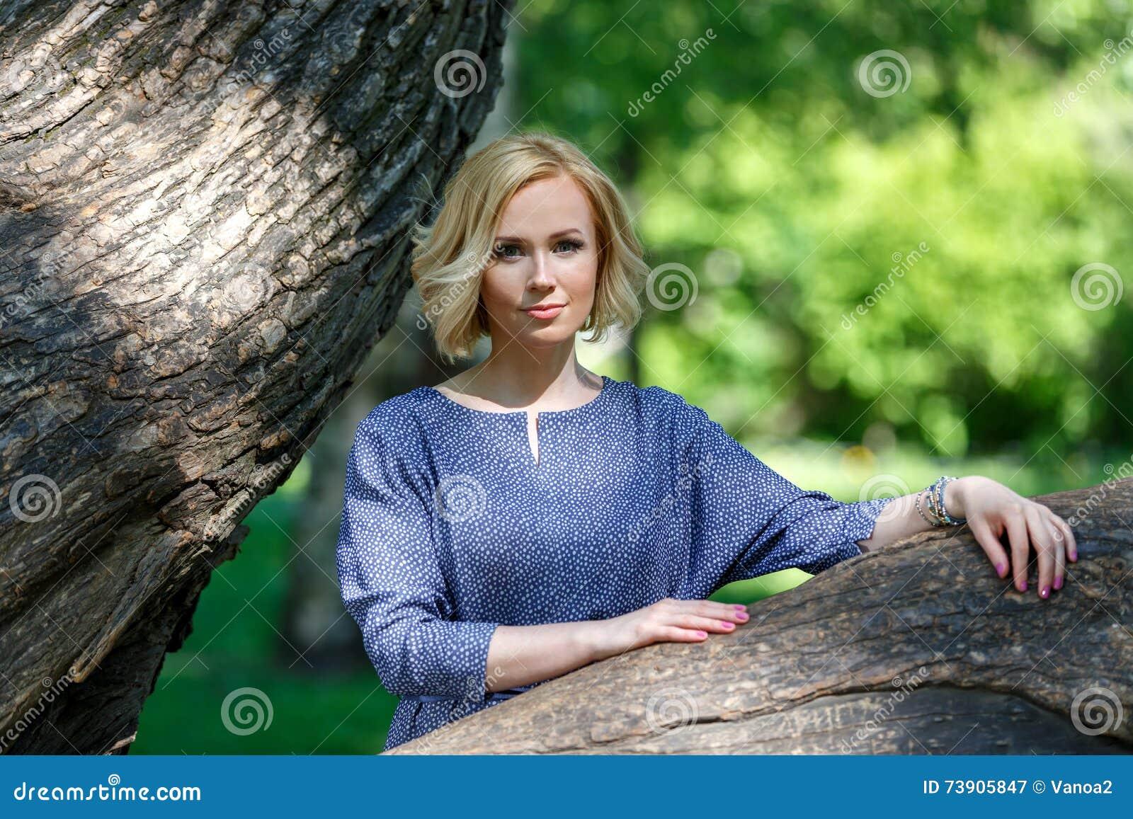 Modelo fêmea novo elegante que inclina-se no Linden grande no parque