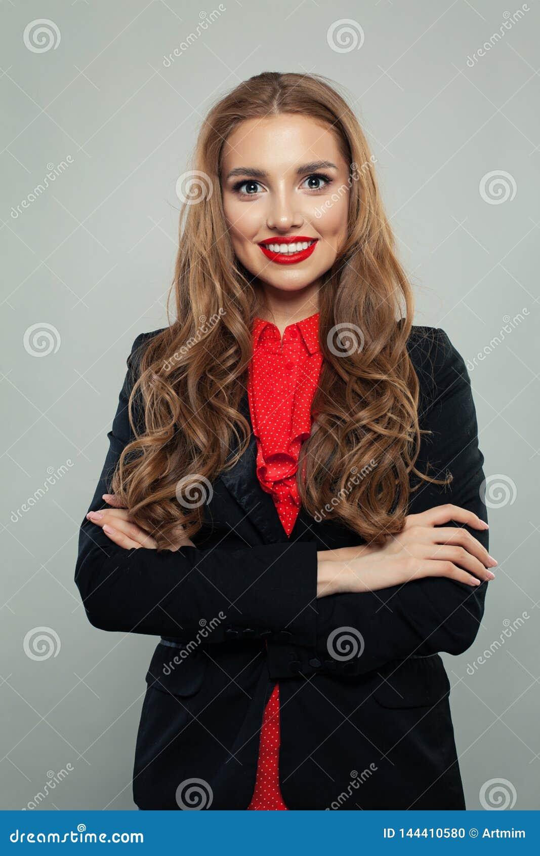 Modelo feliz que sonríe en el fondo blanco Mujer de negocios con los brazos cruzados que llevan el retrato negro del traje