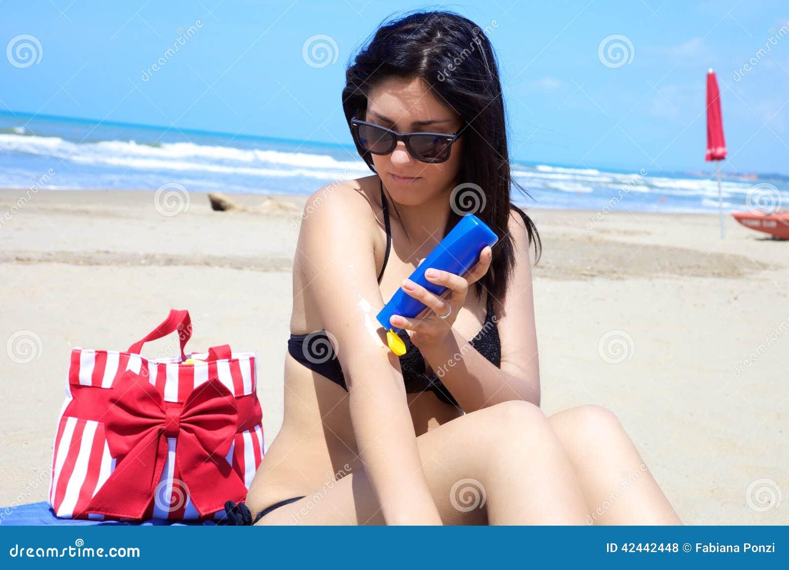 Modelo femenino magnífico que pone la crema del sol en su cuerpo en la playa tropical