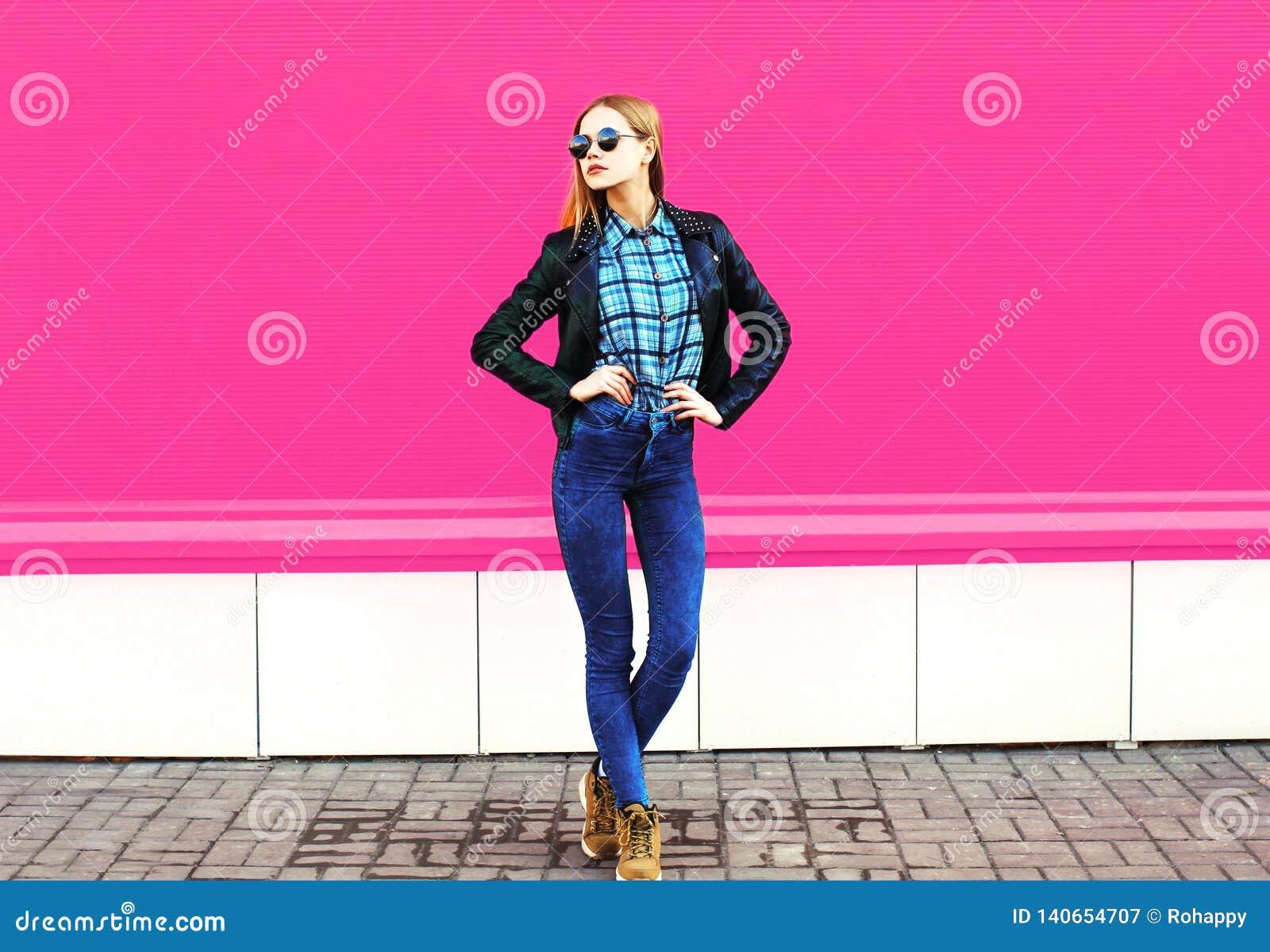 Modelo louro bonito da menina no revestimento vestindo de levantamento completo do estilo do preto da rocha, chapéu na rua da cid