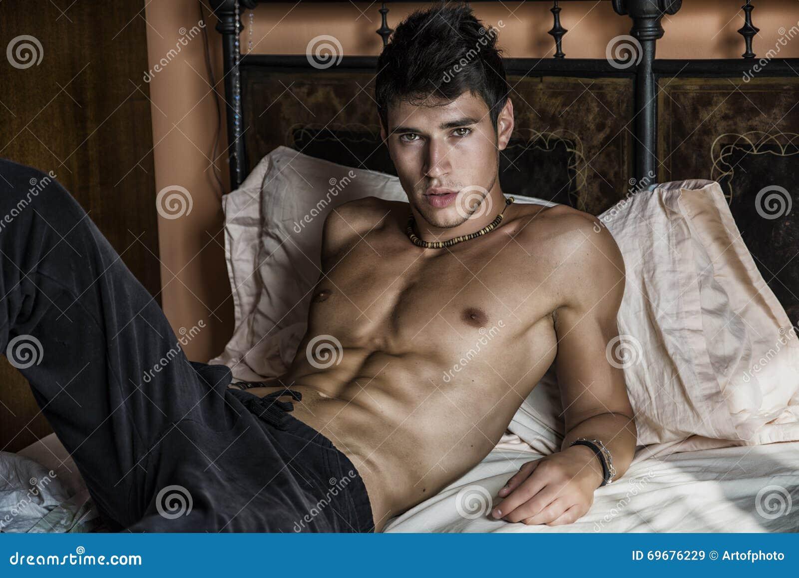 Modelo masculino atractivo descamisado que miente solamente en su cama