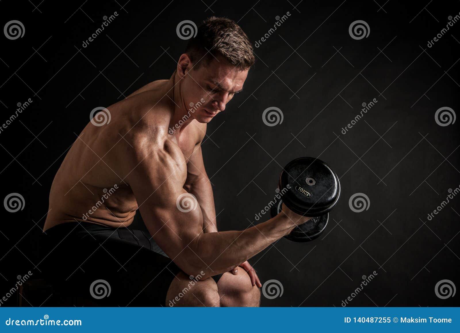 Modelo masculino novo descamisado atlético da aptidão com pesos