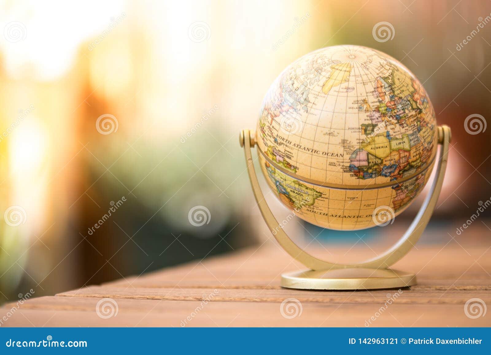 Modelo miniatura del globo en una tabla de madera rústica Símbolo para viajar
