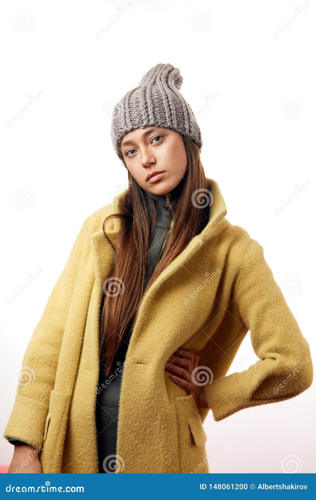 Modelo moreno de la mujer del inconformista de moda en abrigo beige elegante y sombrero gris