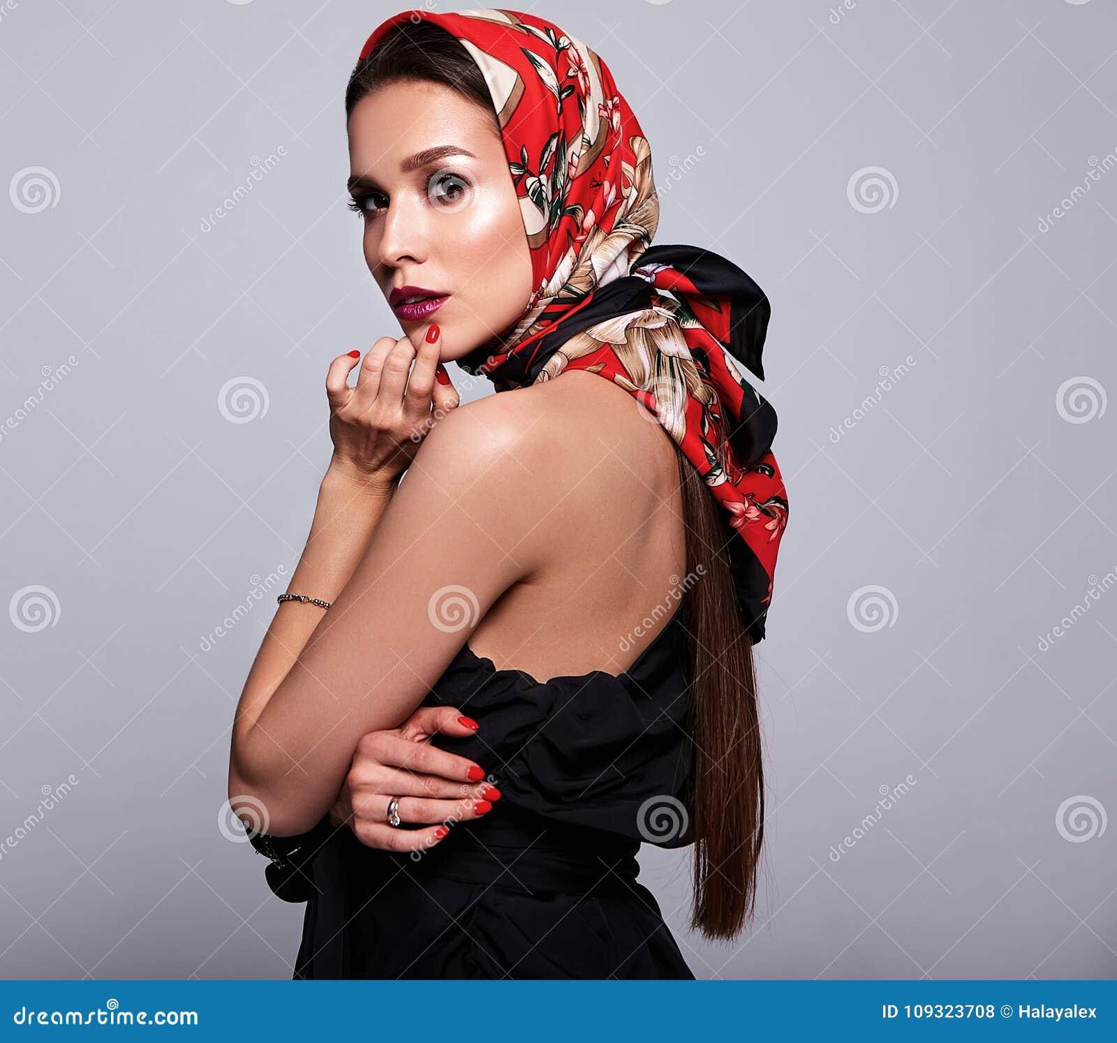 Modelo moreno de la mujer en la ropa elegante que presenta en estudio