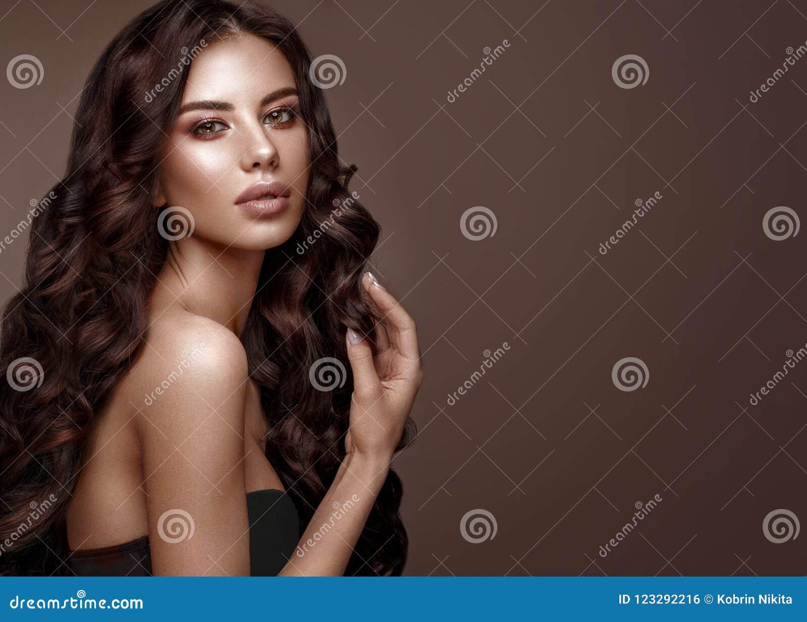 Modelo moreno hermoso: rizos, maquillaje clásico y labios llenos La cara de la belleza