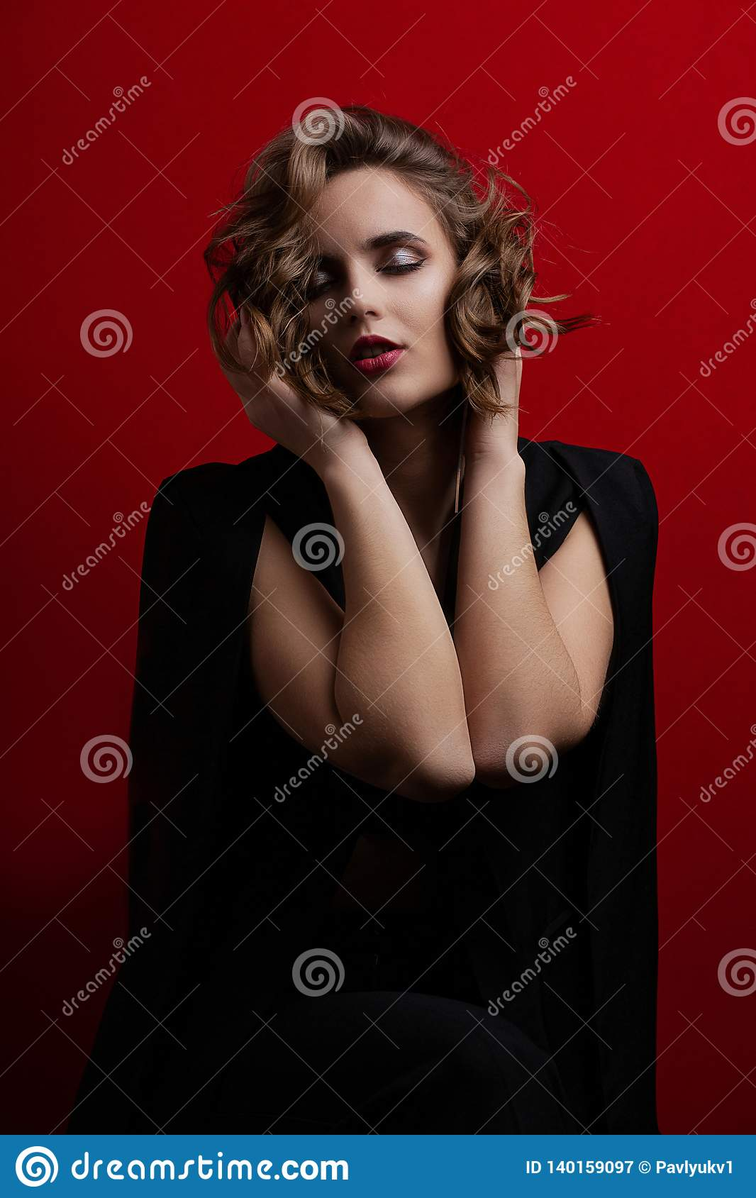 Modelo moreno sensual con el pelo corto ondulado que presenta con la luz del contraste en el fondo rojo