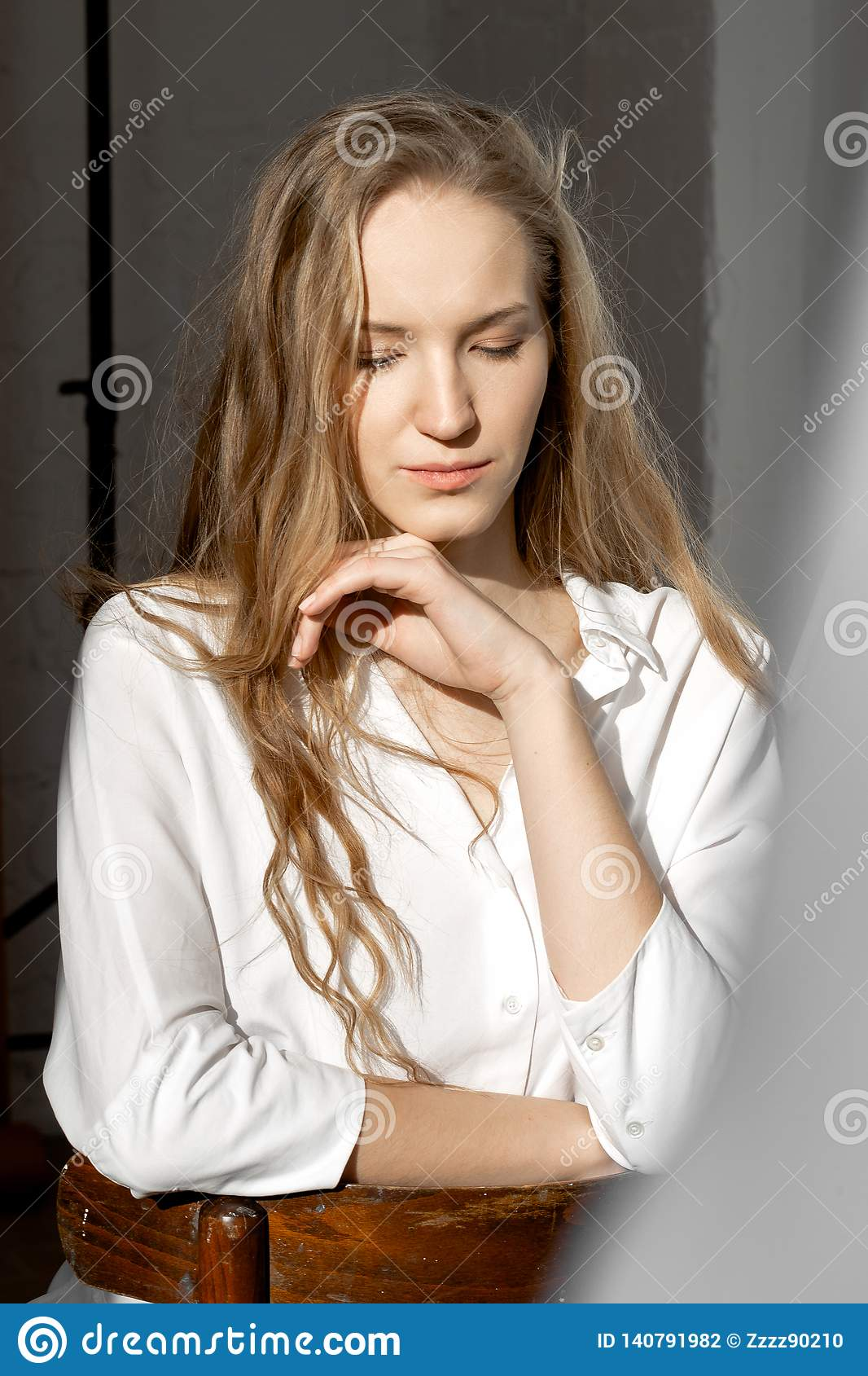 Modelo pensativo triste que olha para baixo na camisa branca