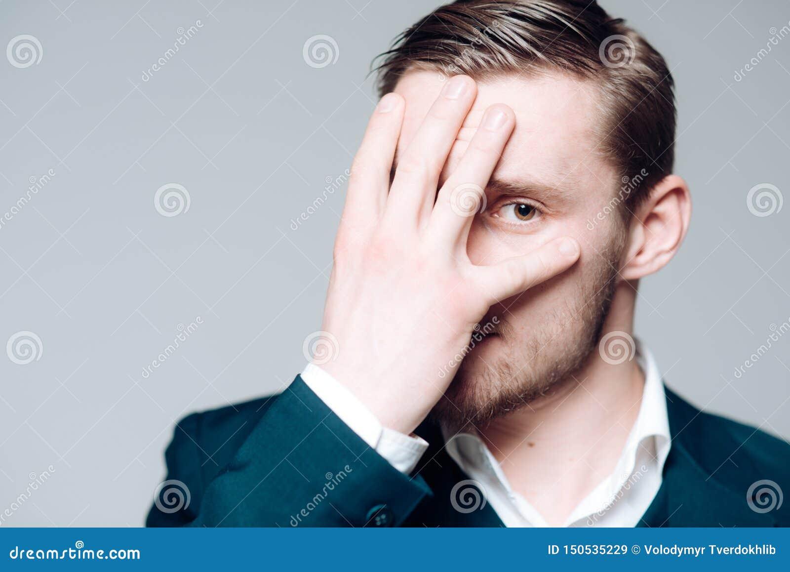 Modelo rubio aislado en fondo gris Individuo barbudo con los ojos pardos que cubren su cara con la palma