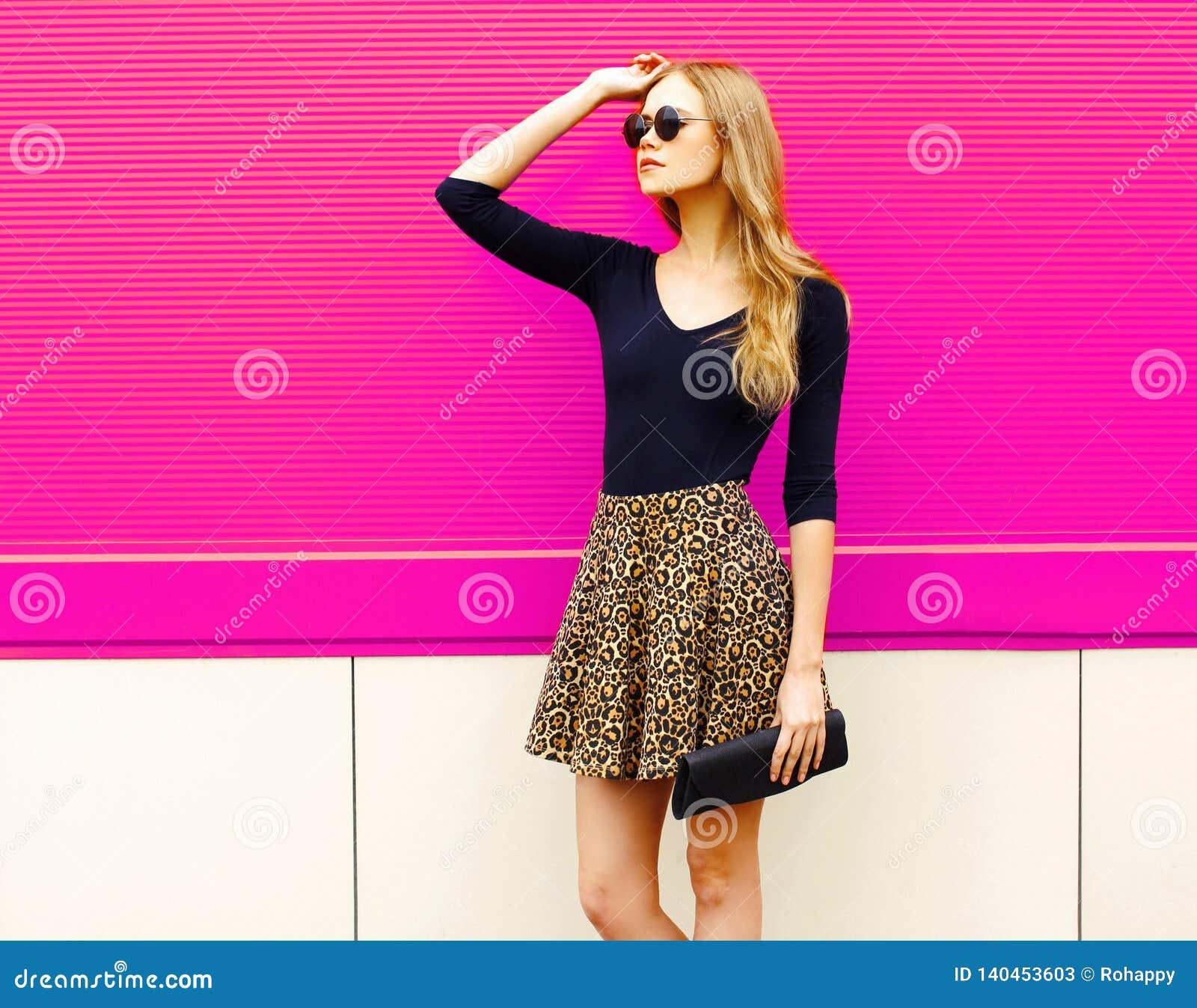 Modelo rubio hermoso de la mujer del retrato que presenta en la falda del leopardo, gafas de sol con el embrague del bolso
