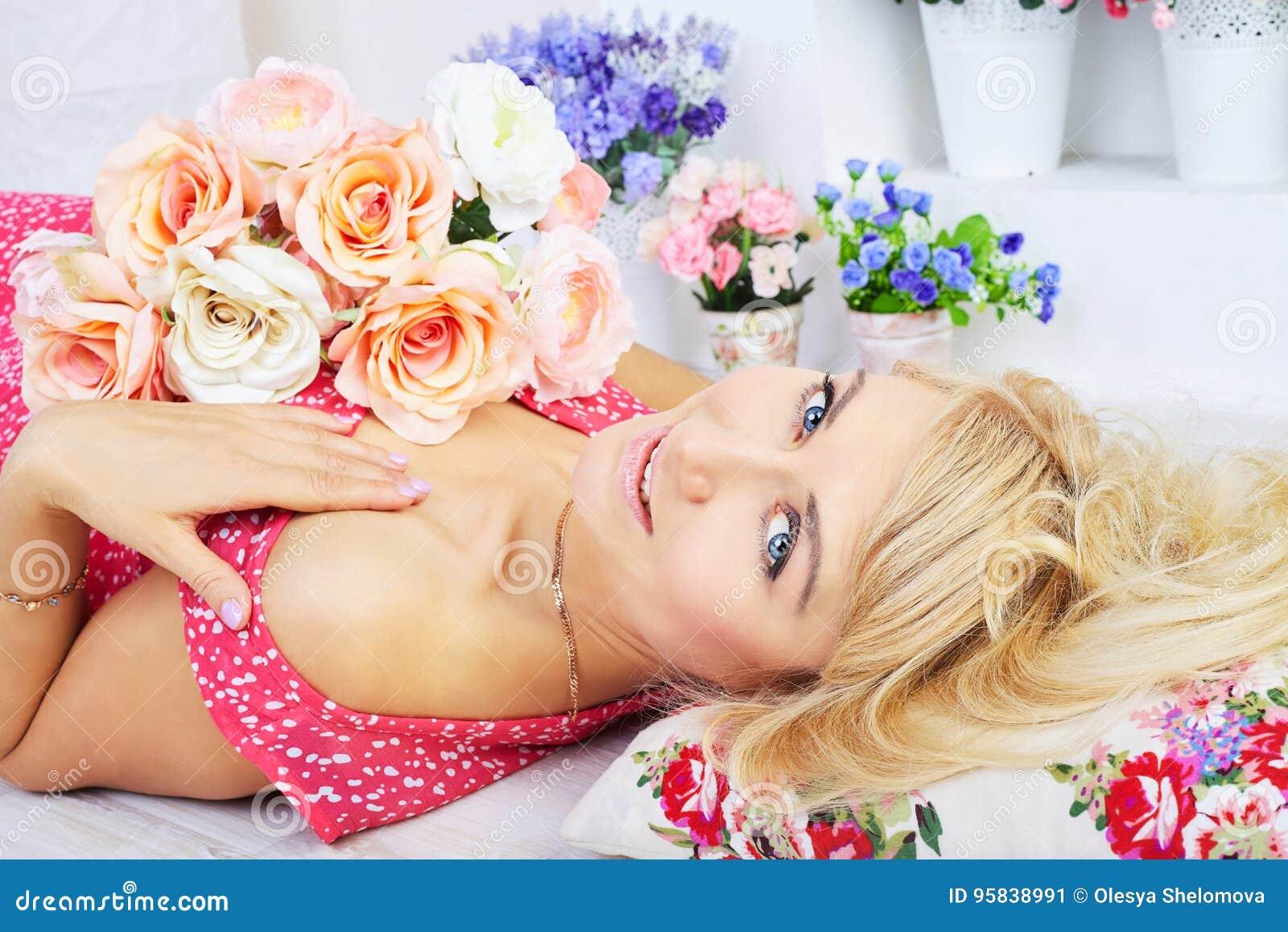Modelo rubio joven sonriente que presenta entre las flores