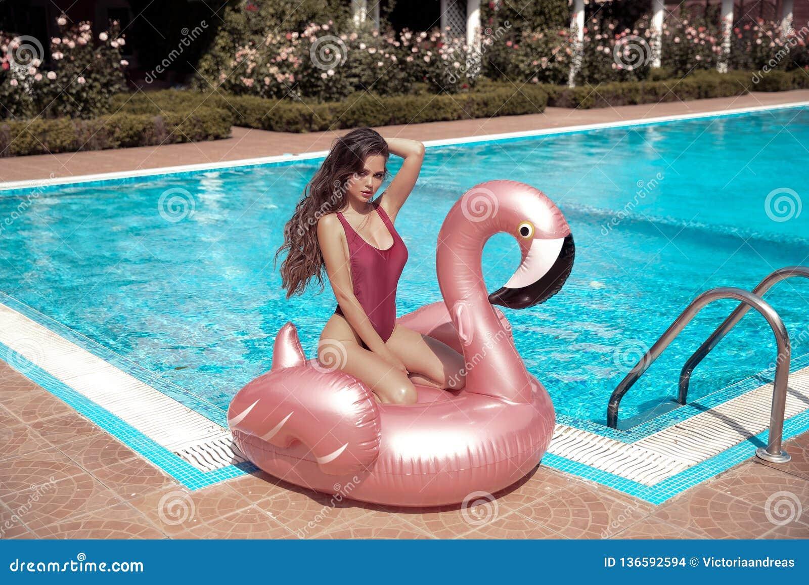 Modelo  sexy  da menina do biquini que aprecia no colchão cor-de-rosa gigante inflável do flutuador da associação do flamingo no