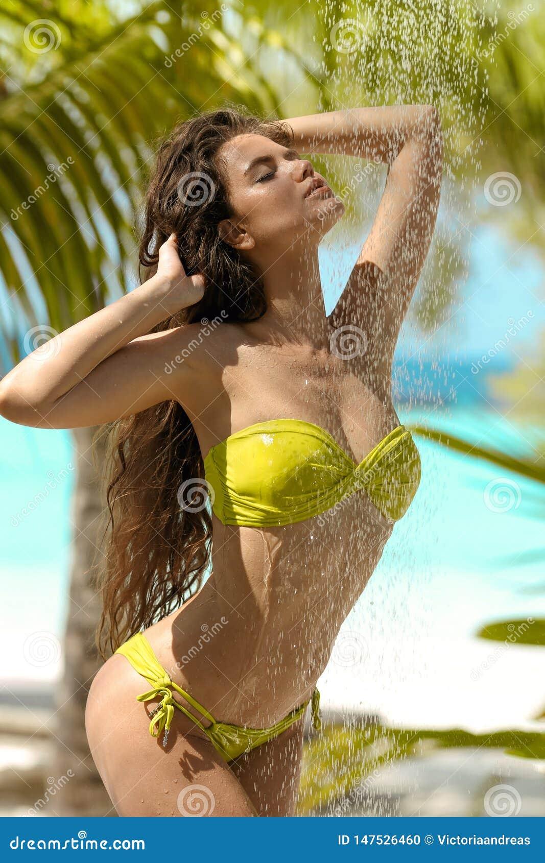 Modelo  sexy  molhado despreocupado do biquini que aprecia o chuveiro tropical exterior Mulher bonita com o cabelo longo que rega
