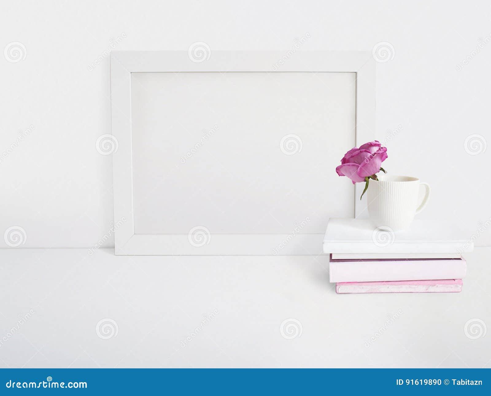 Modelo vazio branco do quadro de madeira com uma flor da rosa em um copo da porcelana e em uma pilha dos livros que encontram-se