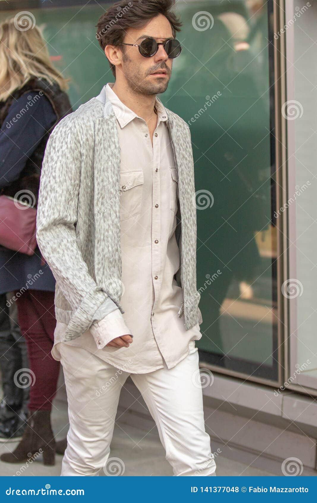 Modelo vestindo um par de calças e de uma camisa sleeved longa bege