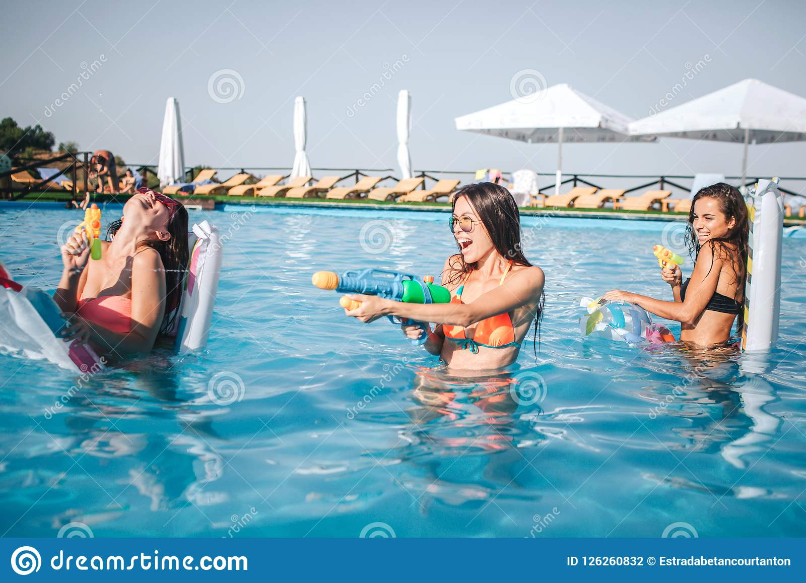 Modelos alegres e engraçados que jogam na piscina Guardam armas de água nas mãos e em usá-lo A mulher dois está contra