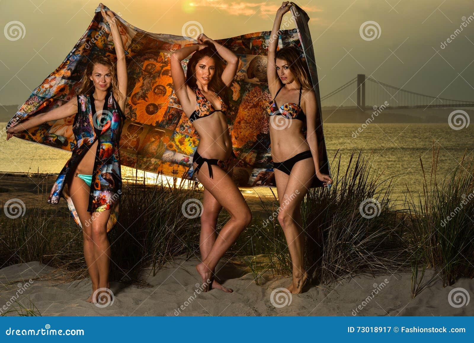 Modelos jovenes hermosos que llevan los bikinis que presentan en la playa de la puesta del sol