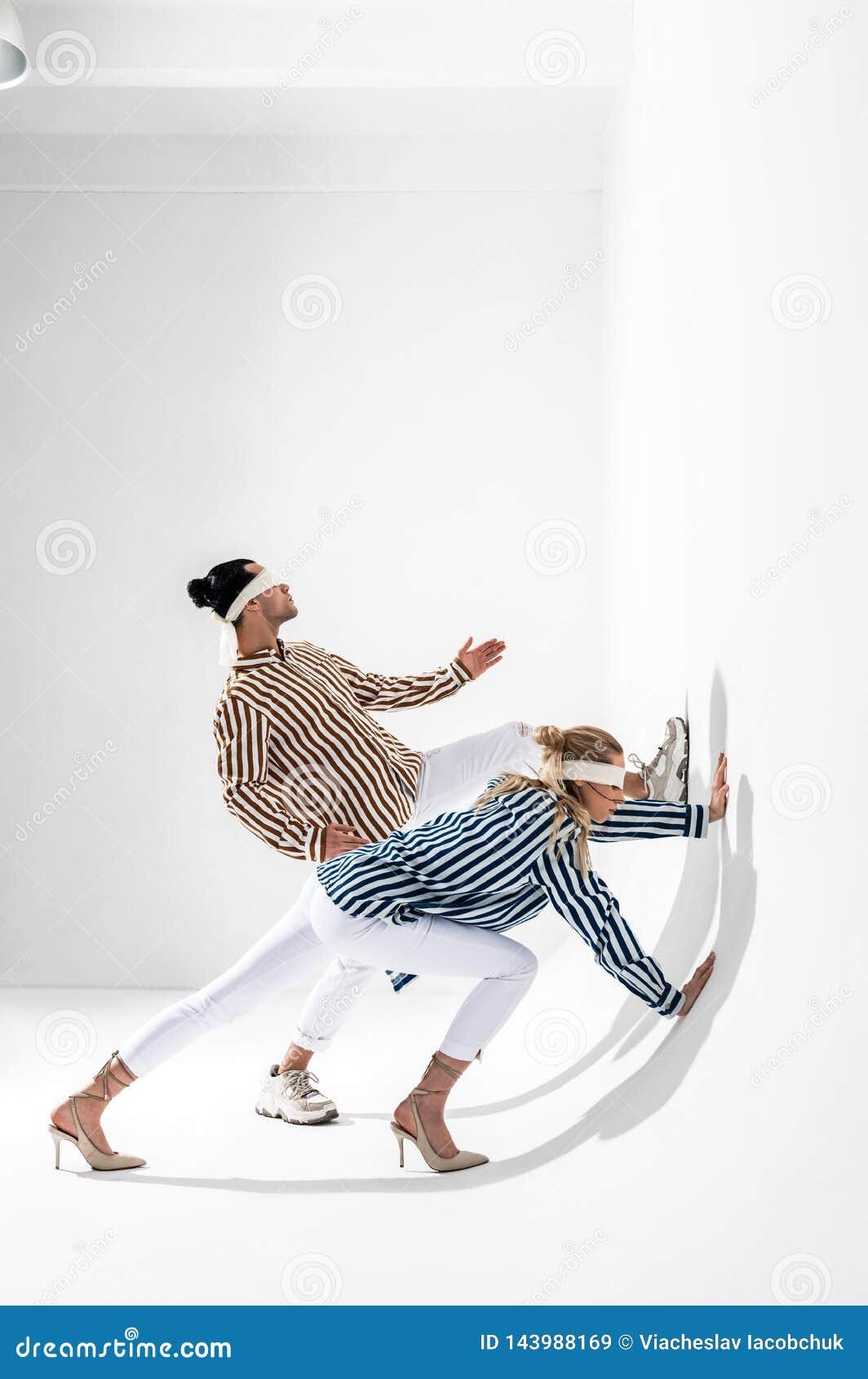 Modelos que vestem as vendas que levantam para a sessão de foto criativa da gravidade