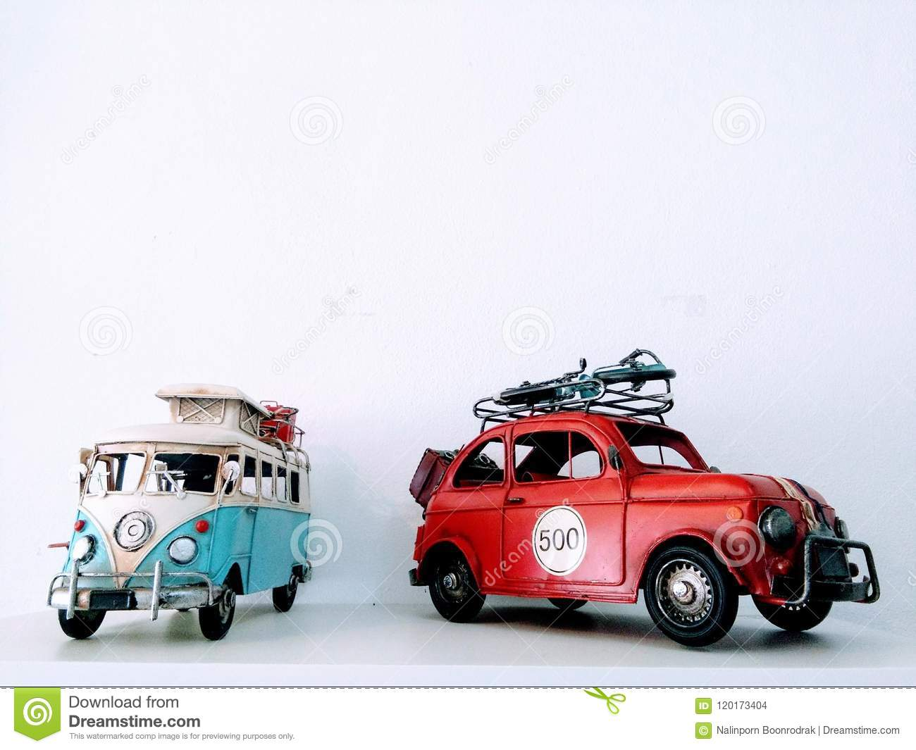 Models of camper van and car on white background