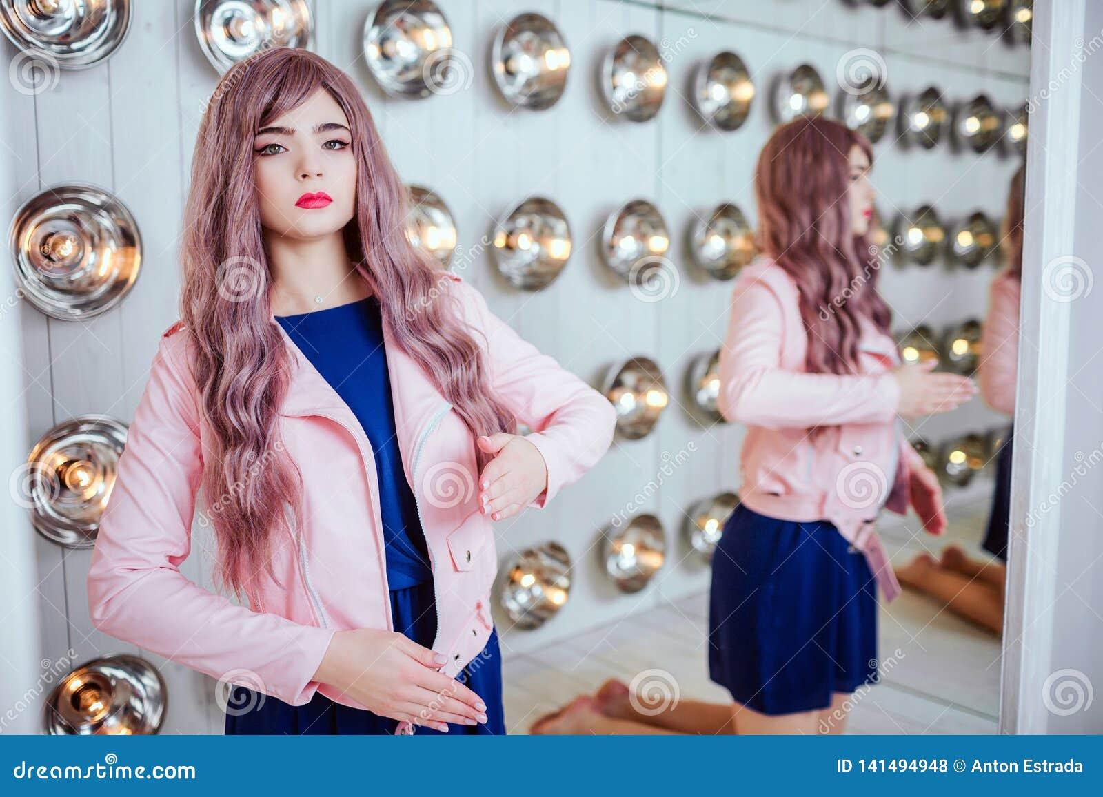 Modemissfoster Fejkar den syntetiska flickan för glamour, dockan med tom blick, och långt lila hår sitter i studion stilfullt