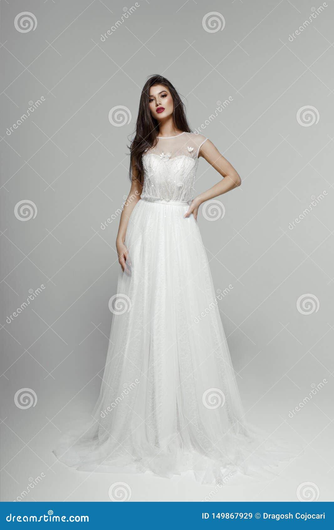 Modemodell i br?llopskl?nning Ung sinnlig brud i den vita klänningen Se kameran som isoleras på en vit bakgrund