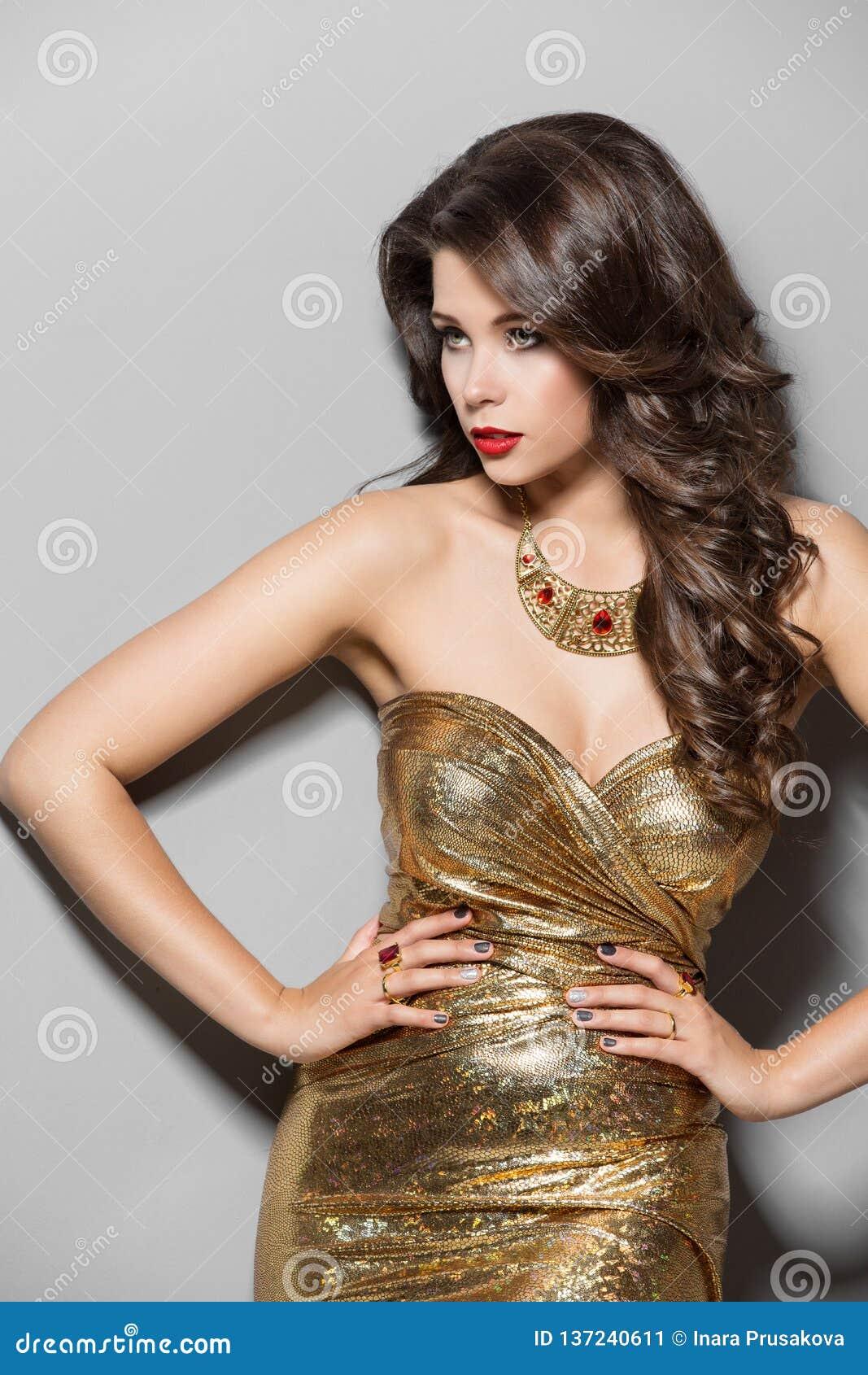 Modemodell i den guld- klänningen, skönhetstående för elegant kvinna