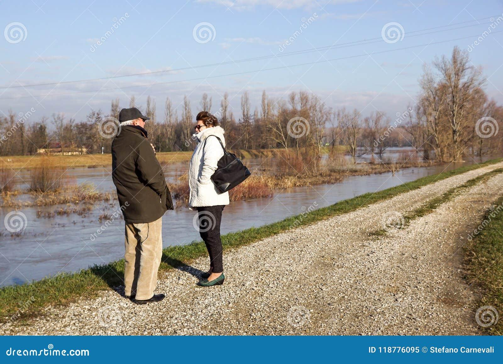 MODENA, ITALIEN AM 16. MÄRZ 2018: älterer Mann und die Mädchen, die als die Fluss ` s Dämme geschwollen werden, laufen nach Tagen