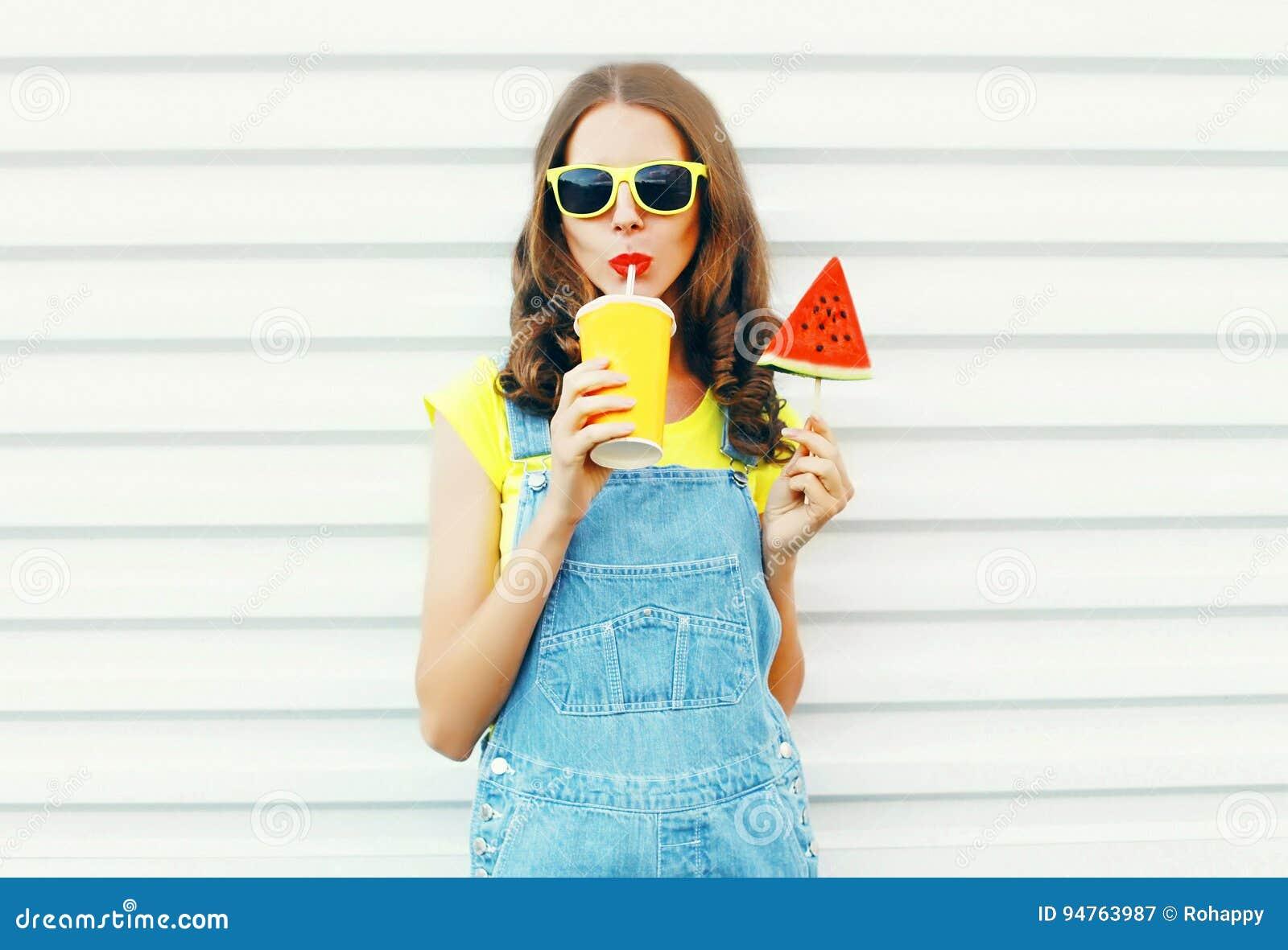 Modeporträt recht, das kühles Mädchen einen Saft von der Schale trinkt, hält Scheibenwassermelonen-Eiscreme