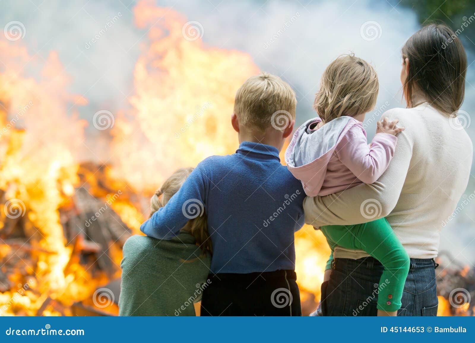 Moder med barn på bränninghusbakgrund