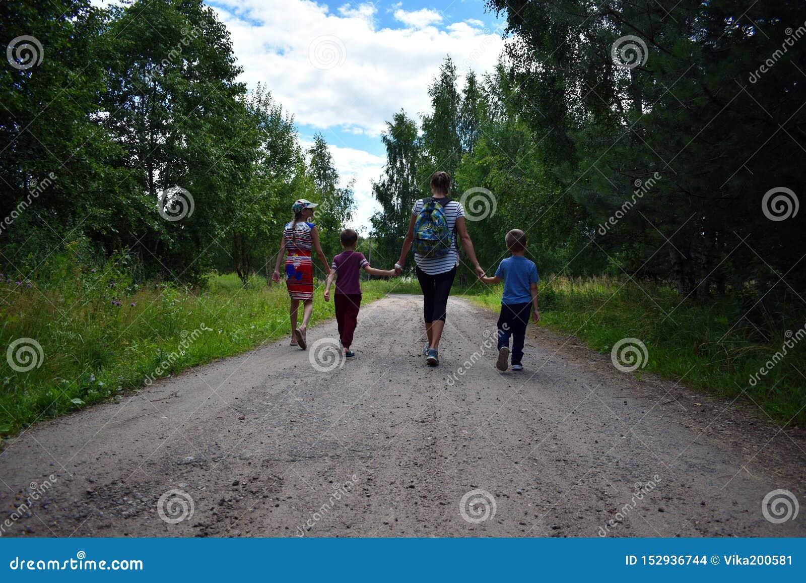 Moder med barn som går i skogen