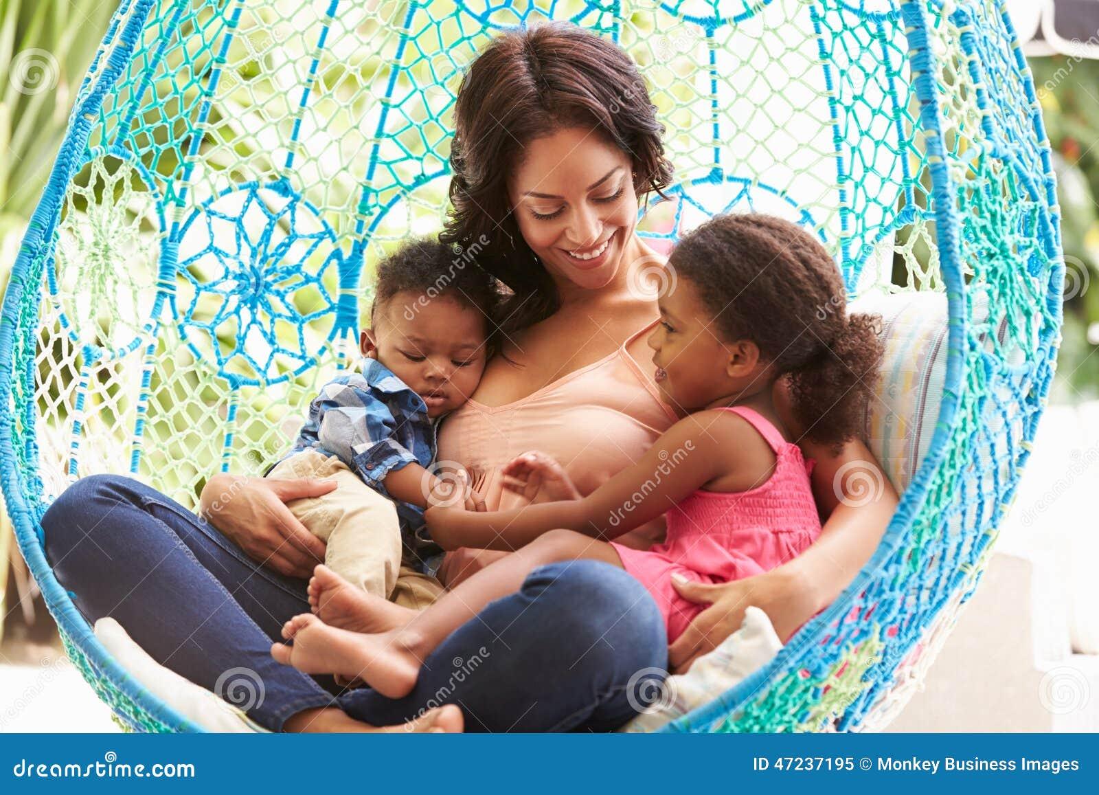 Moder med barn som kopplar av på utomhus- trädgårds- gunga Seat