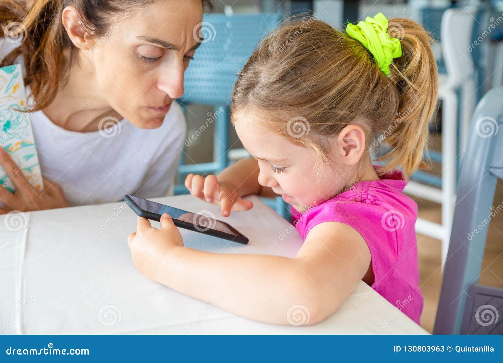 Moder med den bekymrade framsidan som håller ögonen på hennes dotter surfa på mobil