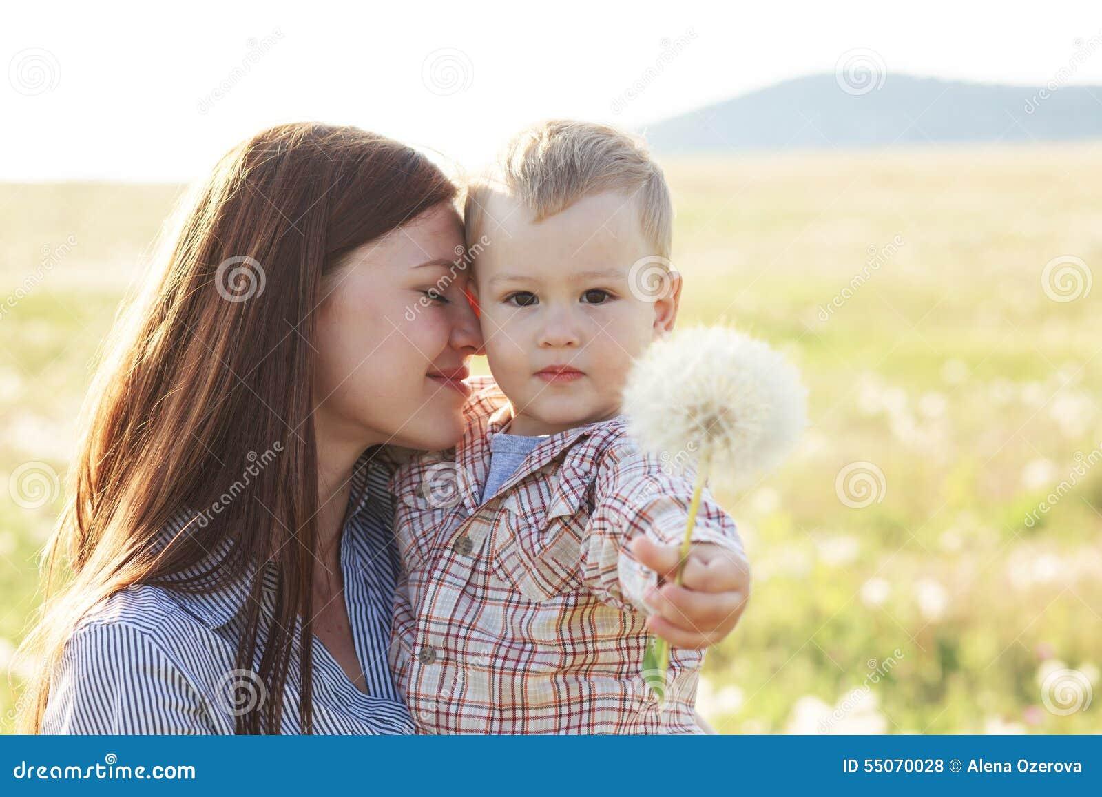 Moder med hennes barn i solljus