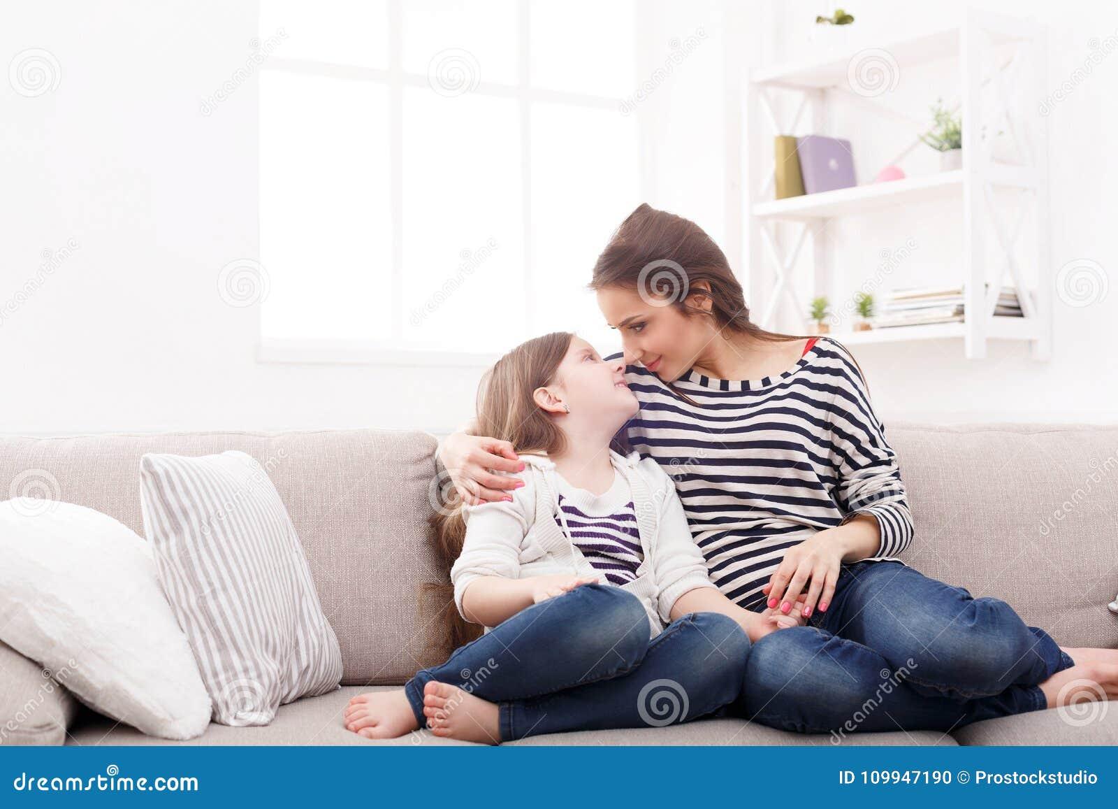 Moder med hennes gulliga lilla dottersammanträde på soffan